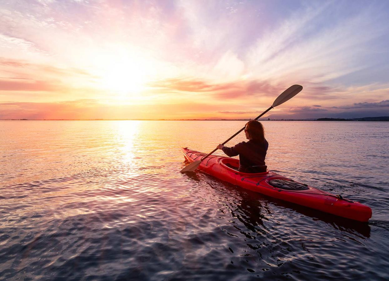 Woman Kayaking at Sunset