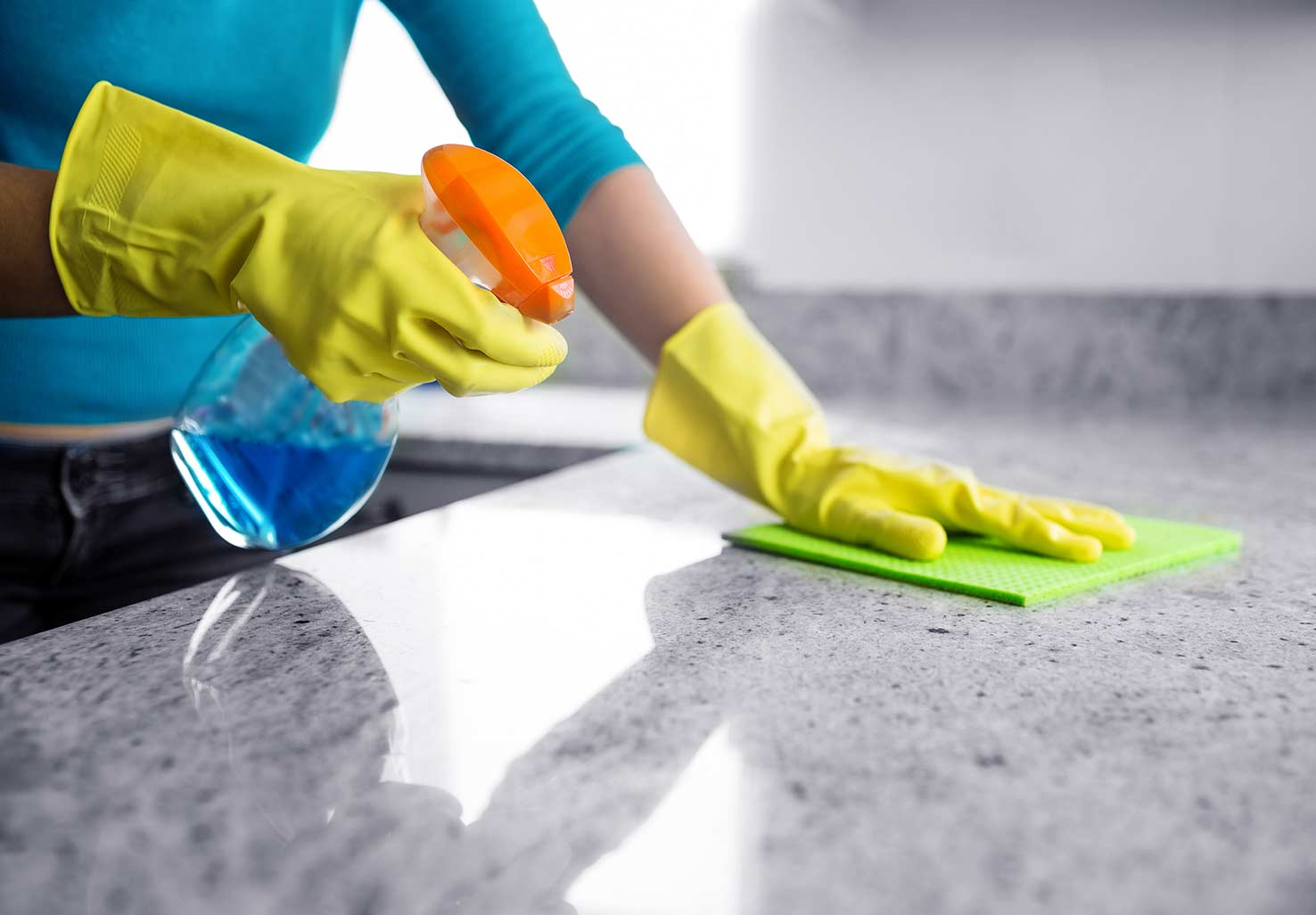 Woman with Gloves Cleaning Countertop